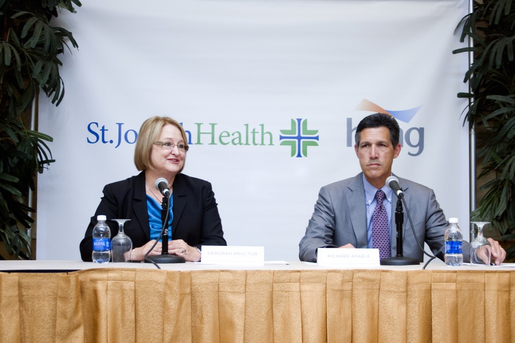 Deborah Proctor, president and CEO of St. Joseph Health, and Dr. Richard Afable, Hoag president and CEO, speak about the affiliation at a conference on Wednesday.