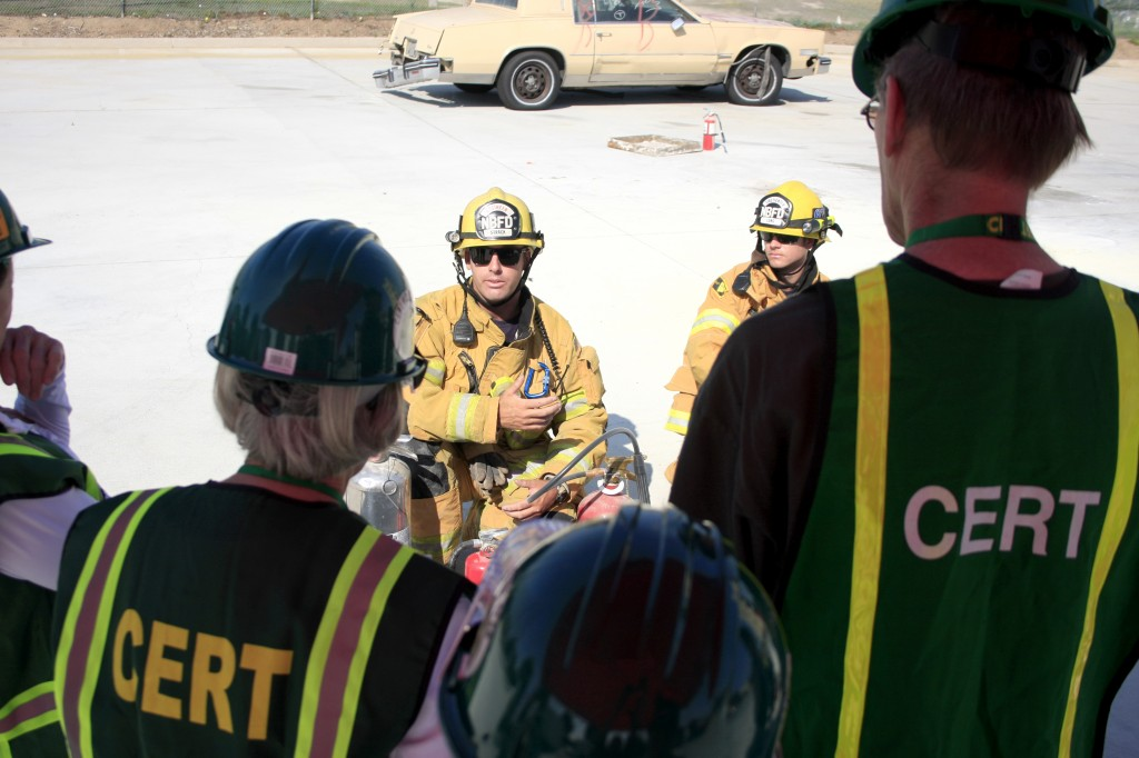 Newport Beach firefighters Jimmy Strack (left) and Jake Long explain the details of fire extinguishers to CERT volunteers.
