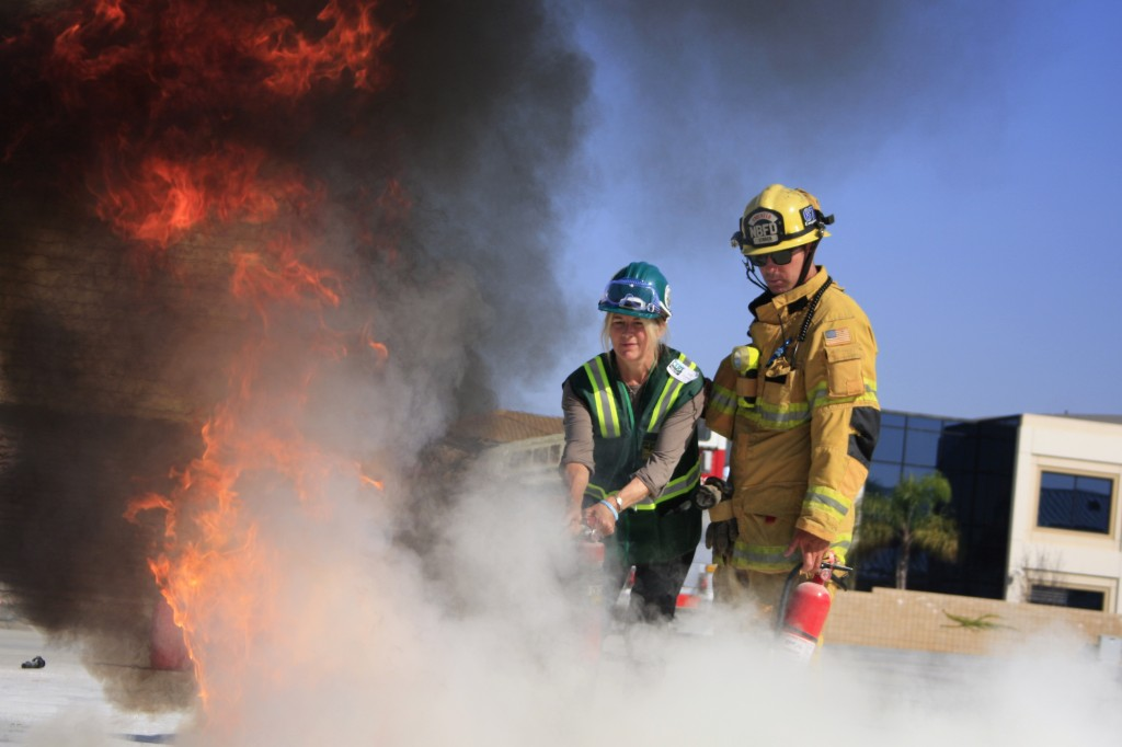 """Newport Beach firefighter Jimmy Strack helps a Community Emergency Response Team volunteer extinguish a fire at Saturday's """"Drill the Skills"""" event. — All photos by Sara Hall"""