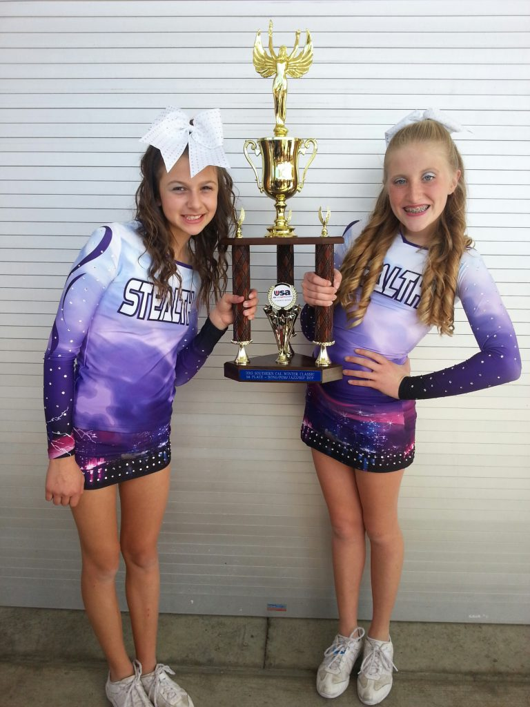 Janey Fales of Costa Mesa and Megan O'Connor of Newport Beach, members of the Stealth cheer team, take a moment to enjoy the fruits of their labors. Their team took first place in a tournament in San Diego last weekend.— Photo by Debi O'Connor