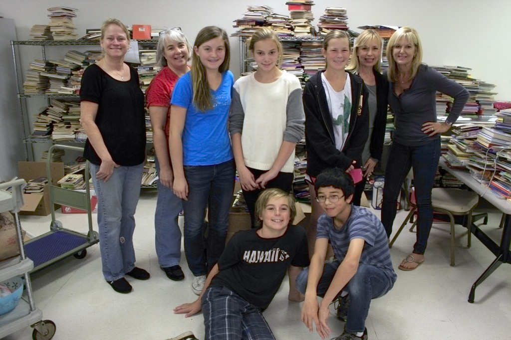 A group from the ALNM pose for a photo while sorting through 7,500 books recently.