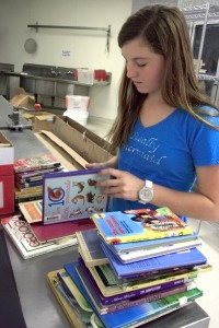 Emily Halphide, 14, from NHHS, goes through donated books to make sure they are in good condition.