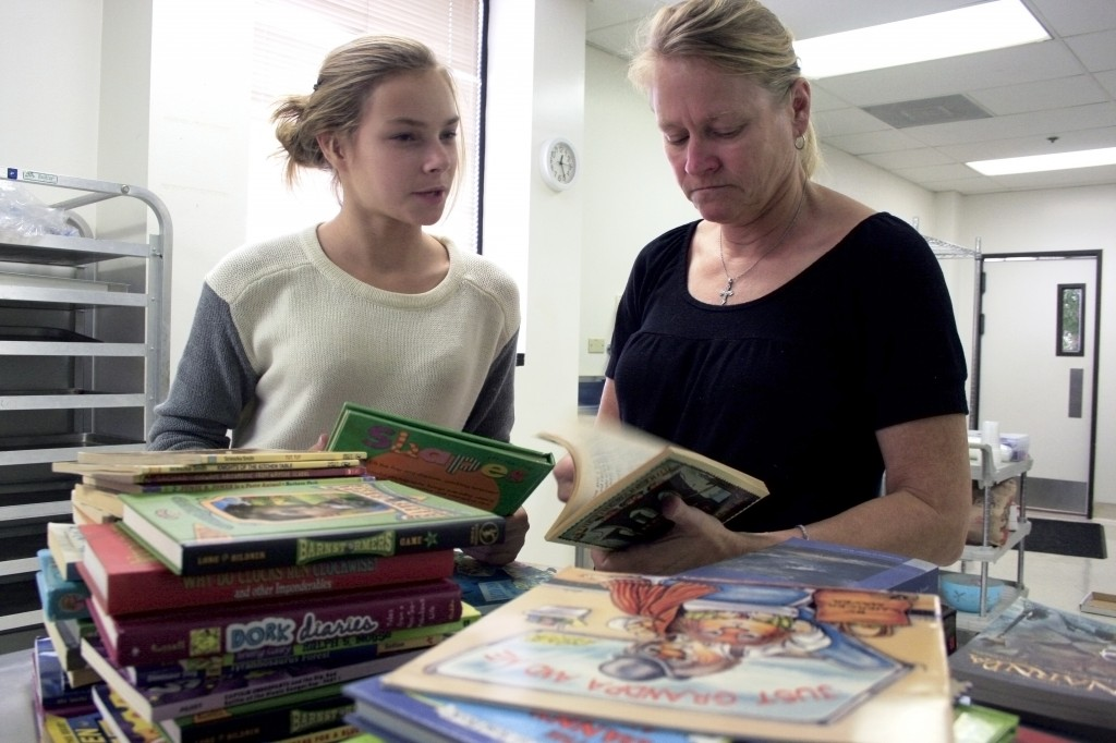 Ellen Kathcart (right) and her daughter Emma, 13, organize books by reading level.