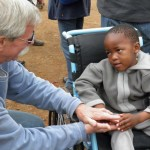 Don Schoendorfer, founder and president of Free Wheelchair Mission, gives a child a much-needed wheelchair.