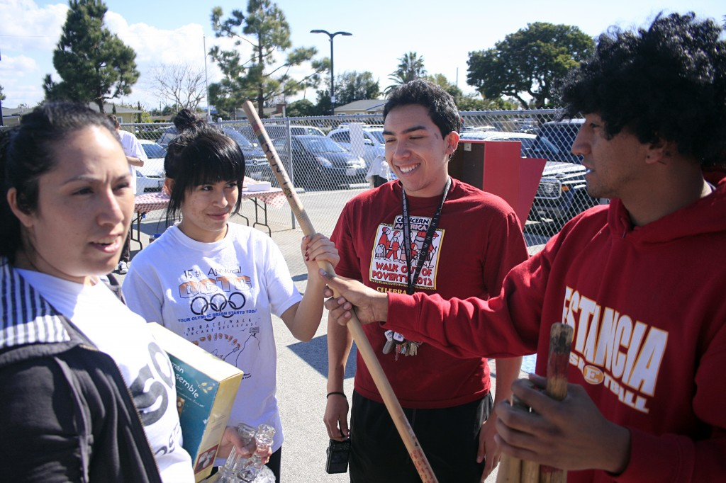 "Arts and music program director of SOY, Eduardo ""Eddie""  Iniestra hands a walking stick to Brenda Vargas, 17, as Frank Alvarez, 18, looks on and they chat about an upcoming SOY event, while Operations Manager of SOY, Silvia Rosales, directs work elsewhere."