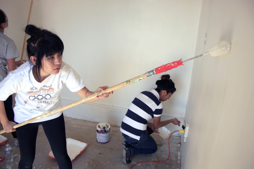 Brenda Vargas, 17, (left) and Wendy Delarosa, 15, from Estancia High School work on painting the SOY office.