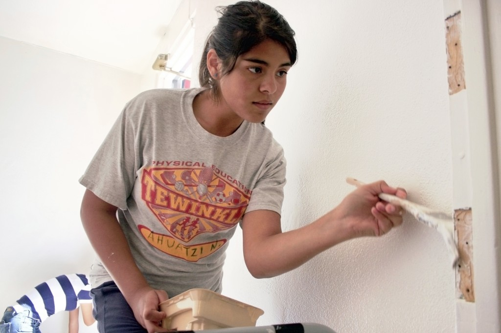 Andrea Ortega, 13, paints the SOY office on Saturday. Ortega, a student at TeWinkle Middle School, likes the dance program at SOY.