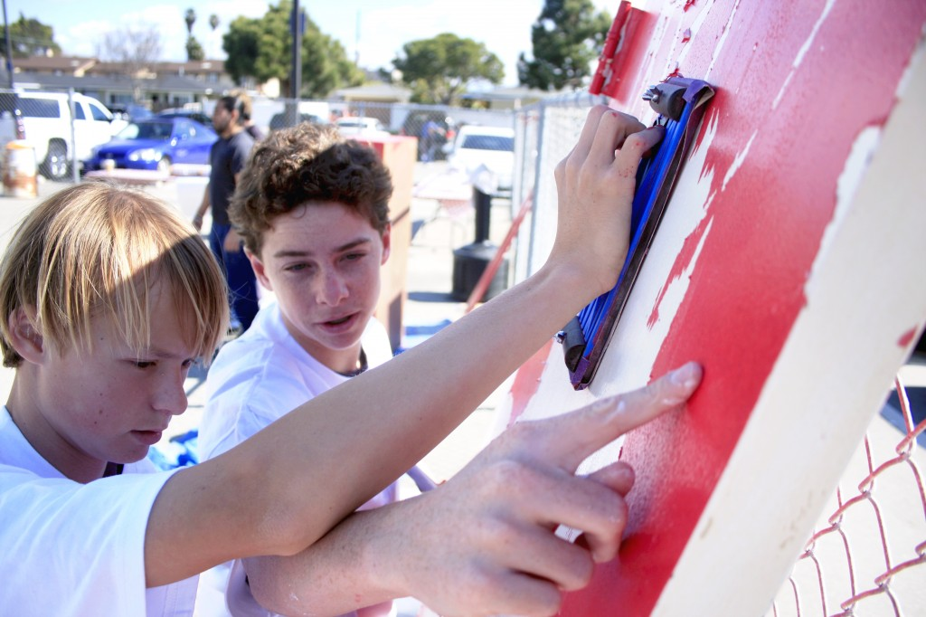 National League of Young Men members Chase Braun (right) and Jack McKasson, both 14 and students at Newport Harbor High School, fix up an old door for the SOY center.