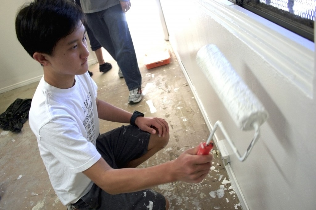 Connor Chung, 15, Sage Hill School student, paints an office wall at SOY. He came with his dad, Henry, for the parent/son NLYM activity.