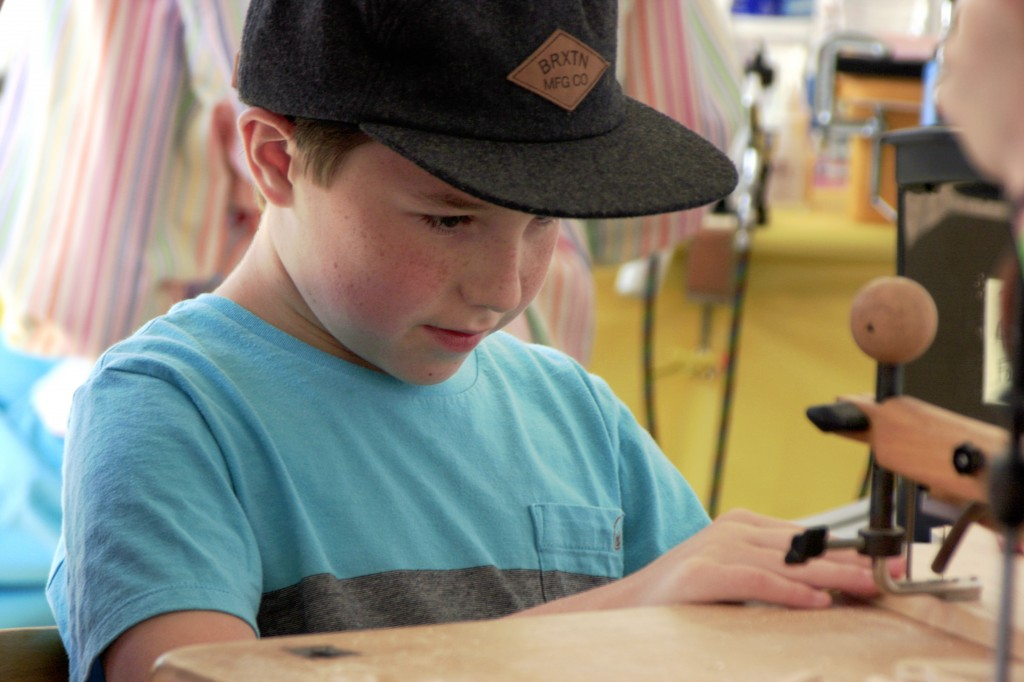 Landon Andrizzi, 11, crafts a wooden toy in the Kids' Zone.