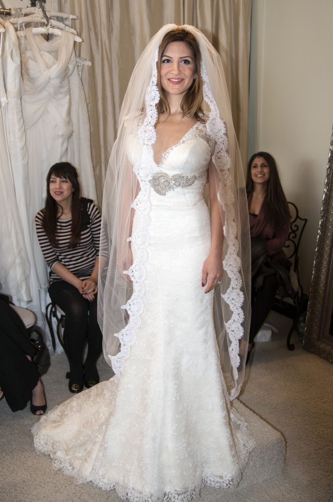 Neda Azarfar tries on a gown at The White Dress in Corona del Mar on Sunday. The shop was participating in the community's bridal walk event. — Photos by Charles Weinberg.