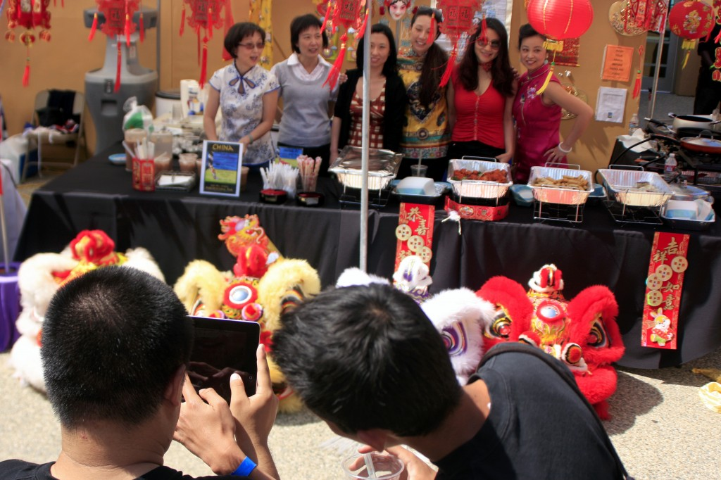Friends and family members take photos of the China booth with the costume heads from the Ane Thanh Chinese Lion Dance group.