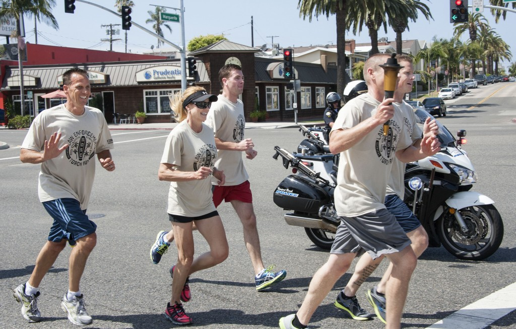 Newport Beach Police Department employees, including chief Jay Johnson (far left), running with the torch for the Special Olympics on Thursday. — Photos by Charles Weinberg
