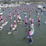 SUP boarders make their way in between boats in the bay.