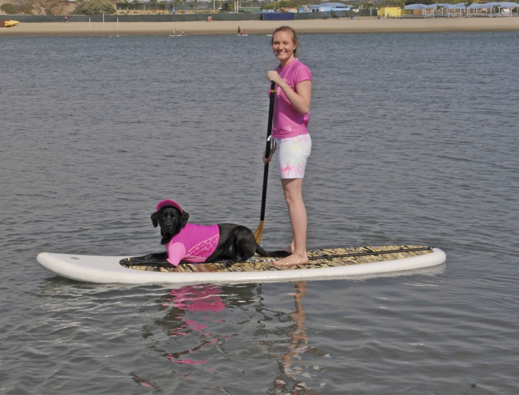 A woman and her dog, both dressed in pink for support, paddle back into Newport Dunes.