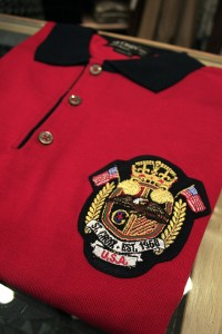 A red collared polo sports the shop's logo.