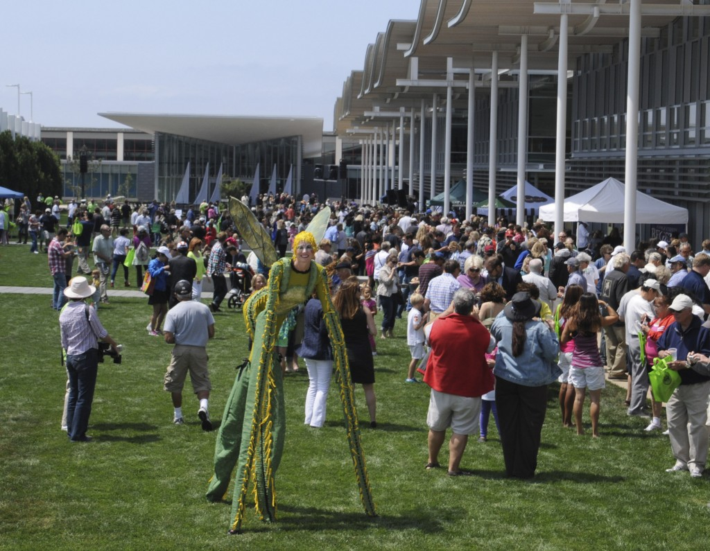 A lady grasshopper on stilts walks through the crowd at the civic center event. — Photo by Lawrence Sherwin