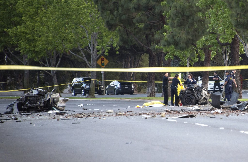 Law enforcement investigators sort through the wreckage of the single vehicle accident on Jamboree Road that killed five Irvine teens Monday evening. — Photo by Charles Weinberg