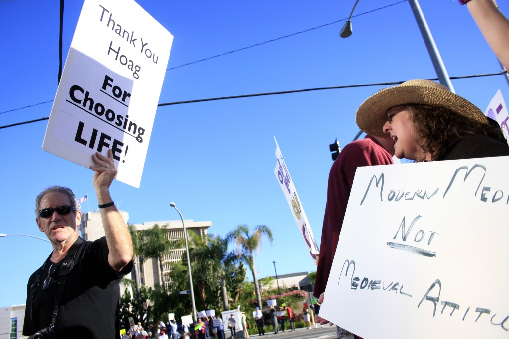 A Hoag Memorial Hospital Presbyterian supporter (left) and a protestor wave signs at each other outside the hospital on Thursday.  — Photos by Sara Hall