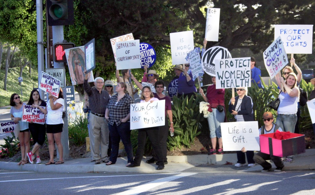 A mixture of both Hoag supporters and protestors congregate at the corner of Hospital Road and Placentia Avenue on Thursday.
