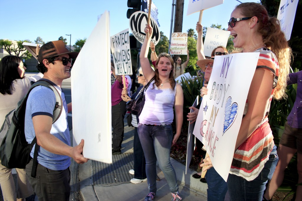 Pro-life demonstrator Paco Frausto of Huntington Beach (left) and pro-choice supporter Erin Morgan of San Diego argue as they wave signs at each other.