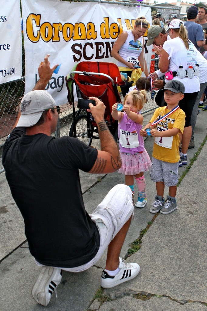 Greg Zinone gets a photo of his kids, Hudson and Hartley, with their medals after the kids race.