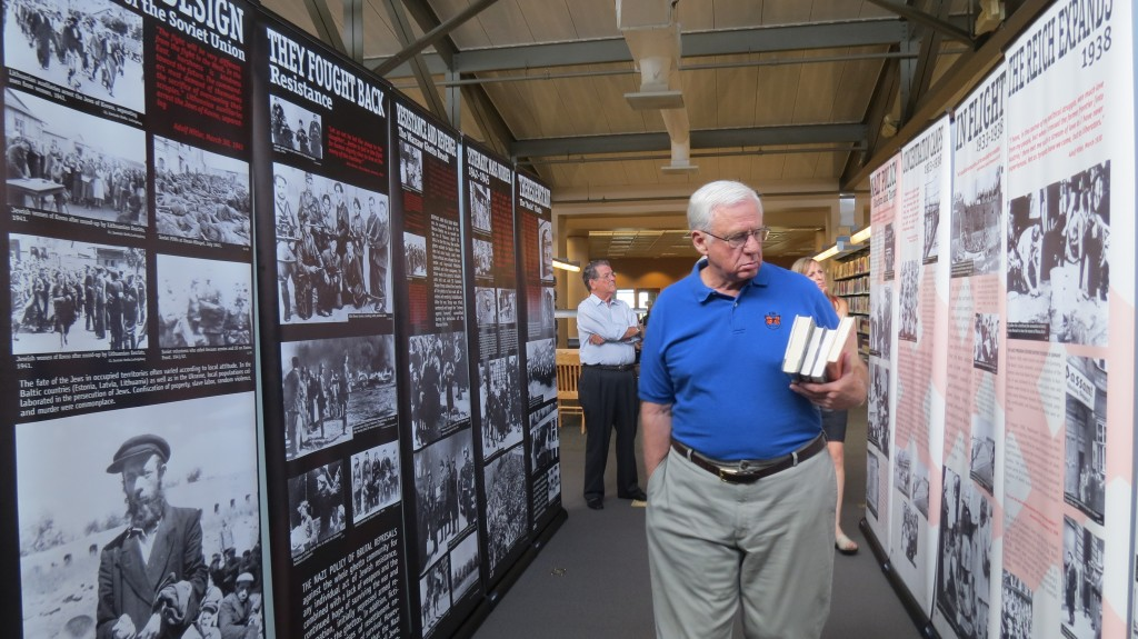 "Visitors walk through the ""Courage to Remember"" exhibit at the Newport Beach Public Library on Monday. The 40-panel presentation documents the Holocaust and will be on display until July 29. — Photos by Elizabeth Greenberg"