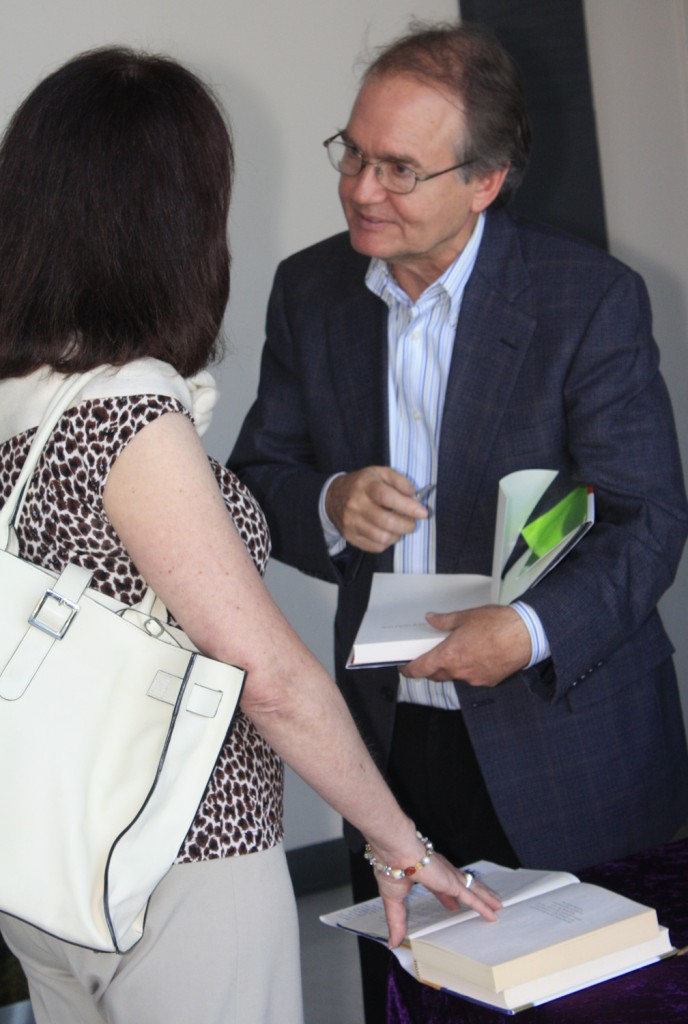 John Gray autographs a book after his presentation