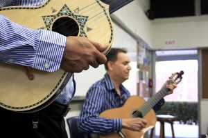 Guitar instructor Jesse Hernandez plays a portion of a song to the Advanced Armonia class as Anthony Zuniga holds his vihuela as he waits to teach the students his part.