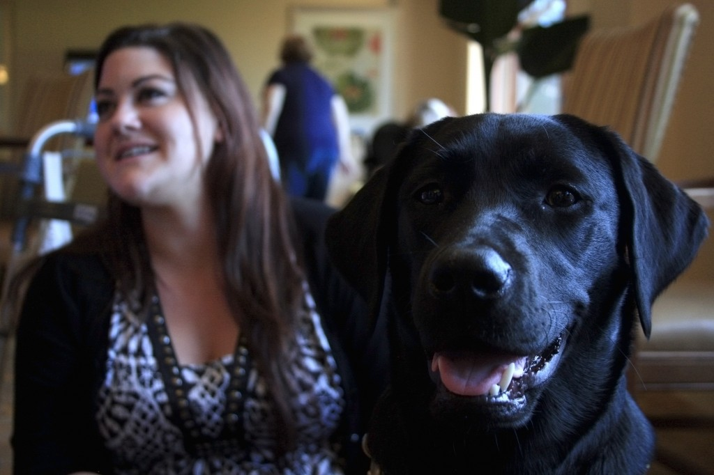 Raja, 8-month-old guide dog in training, with Jessilyn Guajardo, director of activities at Crown Cove senior living community in Corona del Mar.