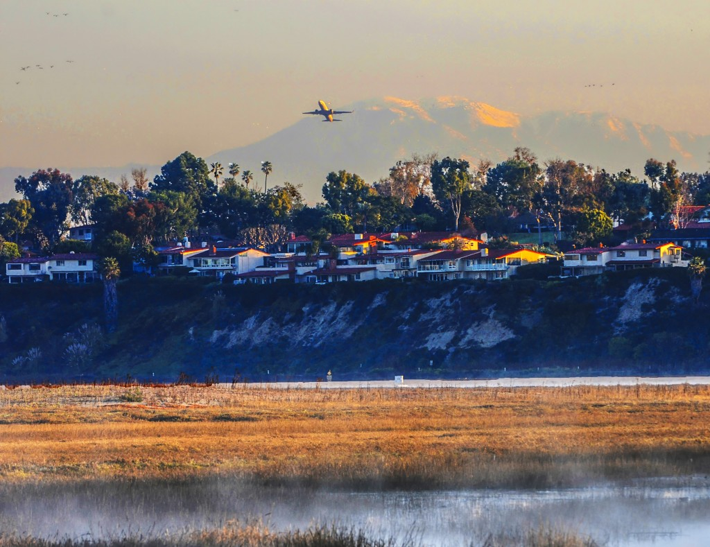 A plane takes off from John Wayne Airport in February, flying over Newport Beach homes and the Upper Newport Bay. — Photo by Lawrence Sherwin