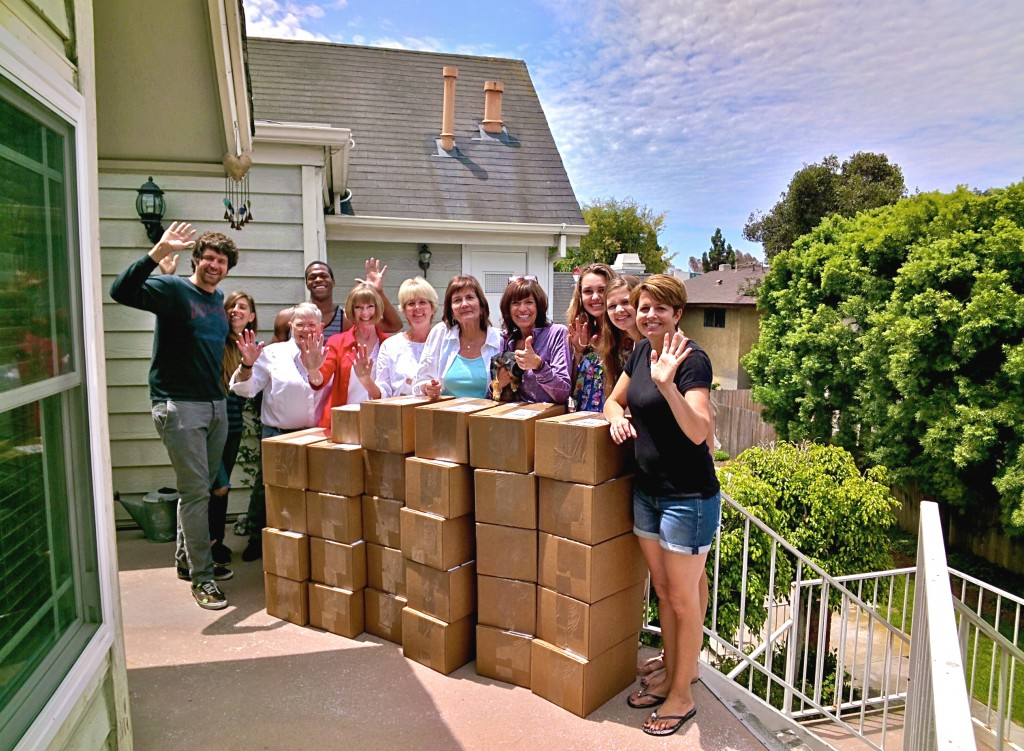 The group of volunteers, including founder Knots of Love founder Christine Fabiani (fourth from right, in purple) with the boxes of caps from that Friday, including the donation from Google employees. They are ready to be shipped out to cancer centers across the U.S. The photo was also taken with Google Glass.