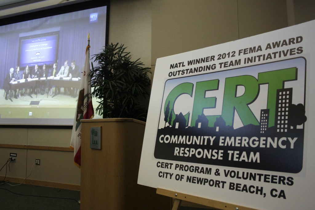 A CERT sign stands at the front of the room at the Newport Beach library as a video of the Champions of Change stream live from the White House in the background.