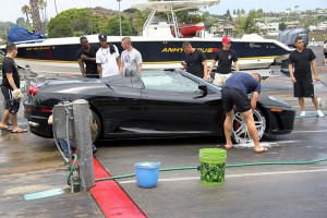 Only in Newport: volunteer members of the 1/1 wash a Ferrari during the July car wash fundraiser. The car's owner offered one Marine a test drive which was accepted without debate. Photo by B.B. Yarborough.