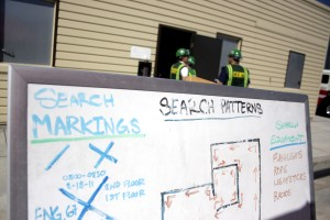 A search and rescue plan is explained on a white board as CERT members wait their turn to search a dark building while crawling on their hands and knees and working as a team.