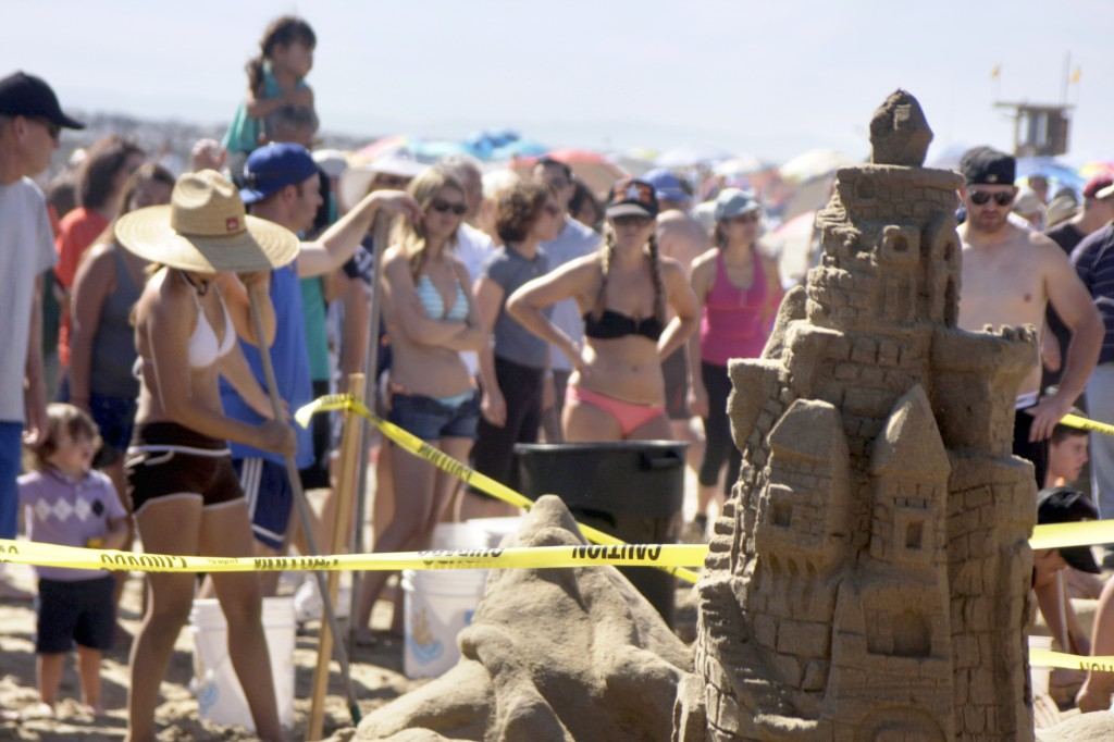 Spectators watch as contestants work on their sand sculptures at the 52nd Annual Sandcastle Contest at Big Corona State Beach on Sunday. — Photos by Sara Hall