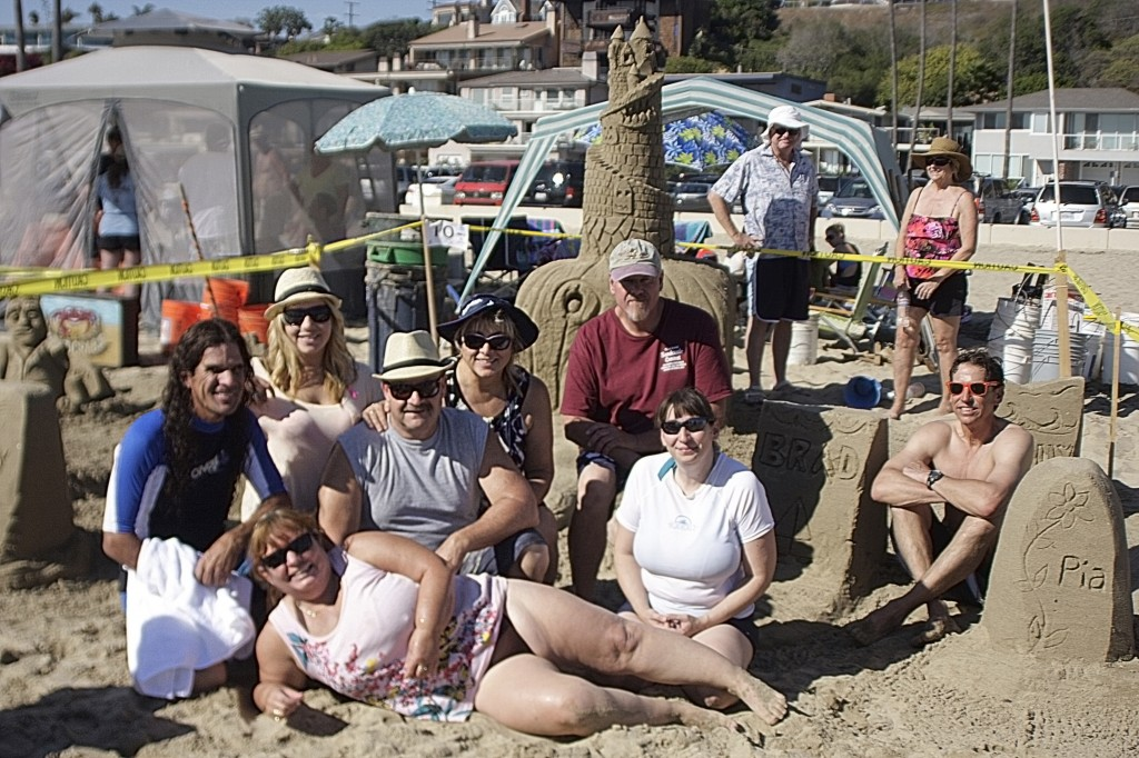 Team Beach Front Homes pose for a photo in front of their spooky sand sculpture.
