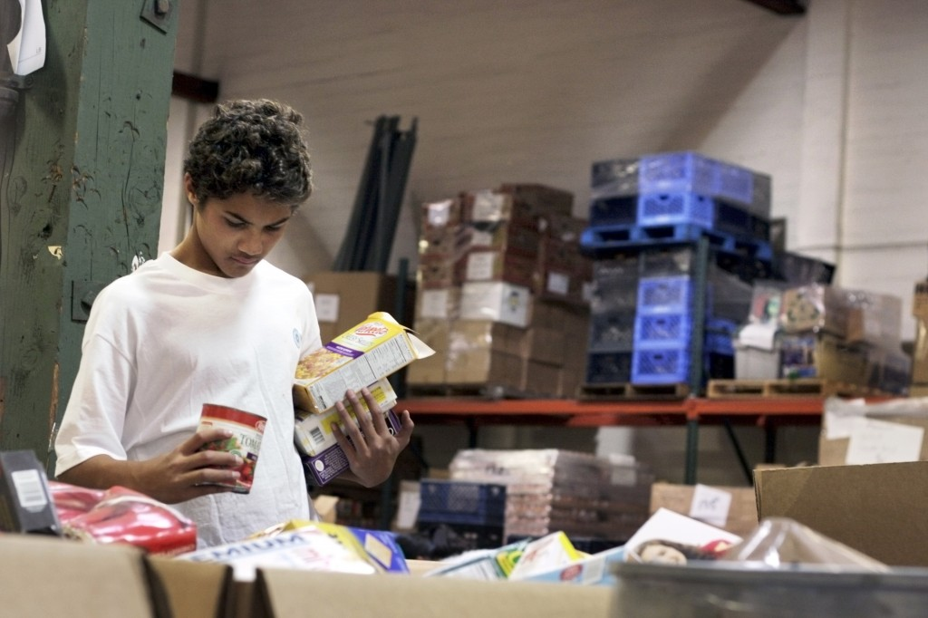 Ea Olotoa scans the bins while sorting donated items at the Second Harvest warehouse on Saturday.