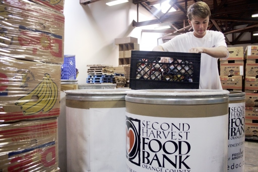 Sophomore Sean Dahl, a member of the National League of Young Men Newport-Mesa chapter, fills up a basket while sorting through donated items at the Second Harvest Food Bank of Orange County warehouse on Saturday. — All photos by Sara Hall