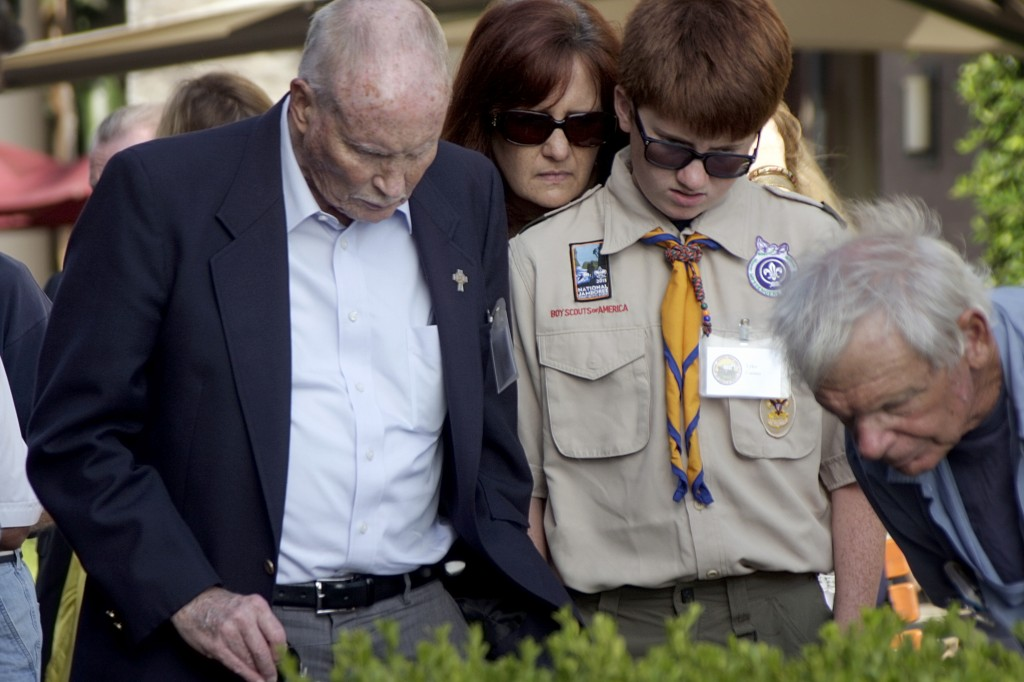 John Feeney, 76, (left) and his grandson Tyler Gaines, 13, who both participated in Boy Scouts of America Jamborees 60 years apart, along with Gaines' mother, Pam, read the monument set up at Fashion Island to commemorate the 1953 event.