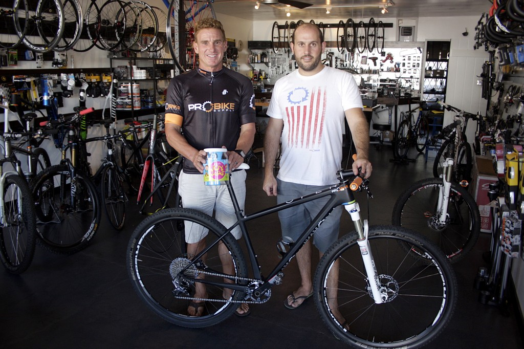 George Vitolo (left) and Mark Cohen in Cohen's store, Pro Bike Supply in Newport Beach, with the bicycle Vitolo will ride in next month's 12 Hours of Temecula endurance mountain bike race in an effort to raise money for charity.