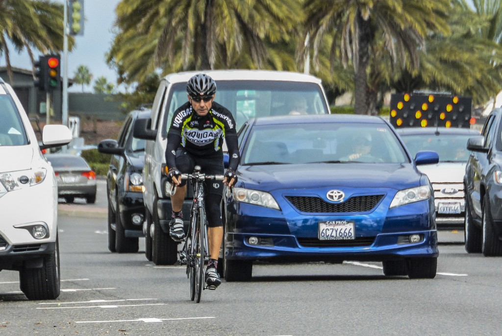 A bicyclist rides along Pacific Coast Highway among moving vehicles. — Photo by Lawrence Sherwin ©