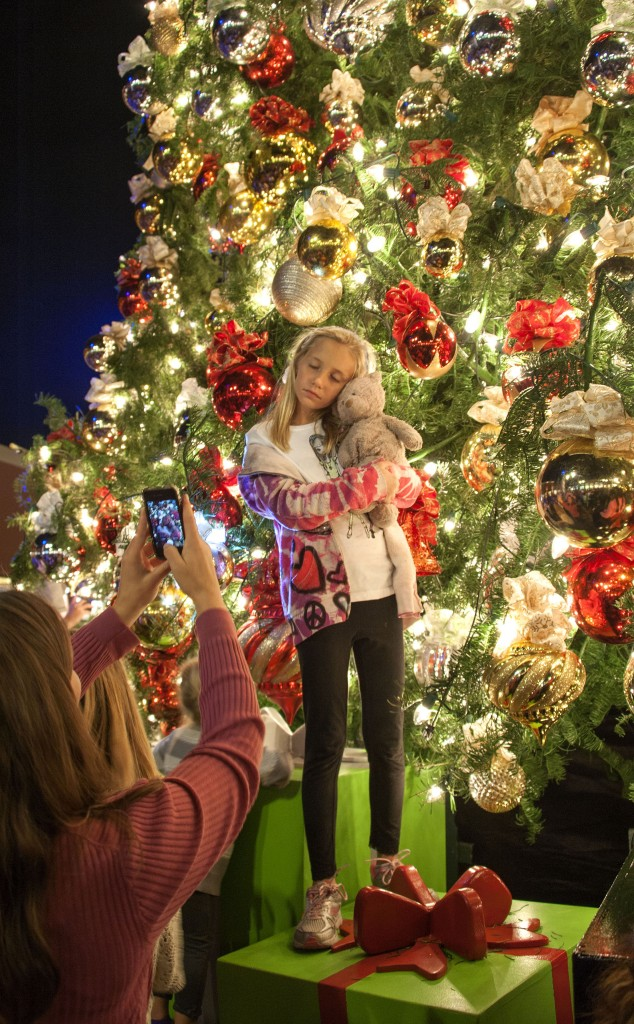 Sydney Dailey, 8, of Irvine, closes her eyes and takes it all in as she poses for photos in front of the tree during the lighting ceremony at Fashion Island on Nov. 15.
