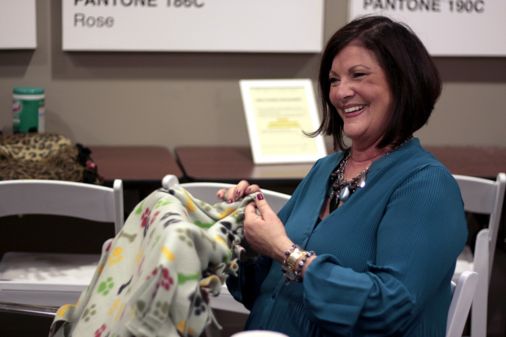Laura Gale, a real estate agent at HÔM Sotheby's Balboa Island office, works on a dog blanket as she talks with colleagues during the company's Day of Giving event on Wednesday.  — Photo by Sara Hall