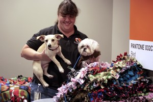 Tammy Osborn, of OC Animal Care, shows two of the shelter's dogs, Barney (left) and Jack Frost, the blankets the group made on Wednesday. — Photo by Sara Hall