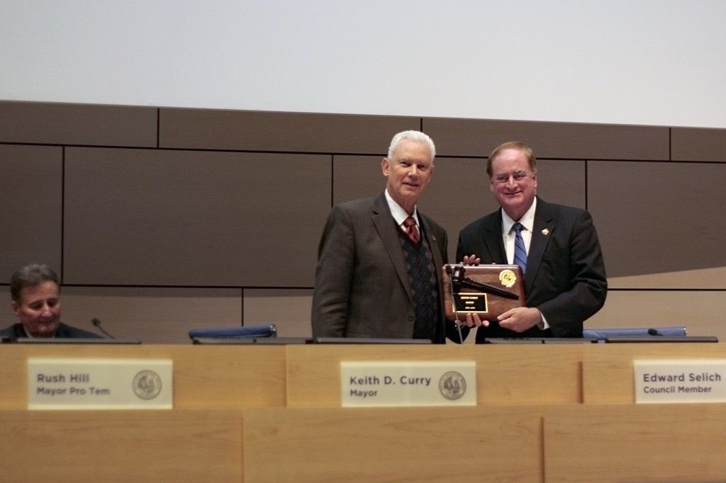 Newly elected Mayor Rush Hill presents a gavel plaque to councilman and outgoing mayor Keith Curry. Mayor Pro Tem Ed Selich looks on from the background.