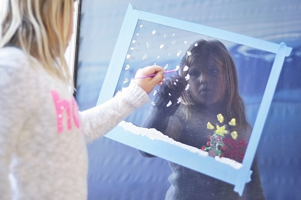 "Chloe Bennett, 8, a third grader at Newport Elementary School, helps ""Paint the Town"" as she creates a snowy Christmas scene on an ExplorOcean window on Wednesday."