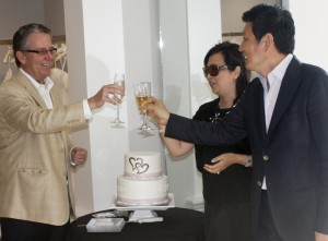 Retail consultant James Fleming toasts Gloria and Kevin Wu at their grand opening celebration.