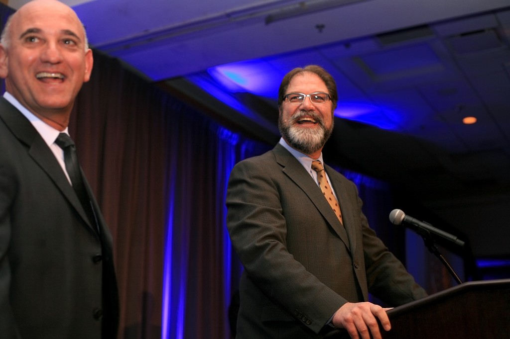 Orange County Supervisor John Moorlach (right) and President and CEO of the Newport Beach Chamber of Commerce, Steve Rosansky, laugh as Moorlach prepares to speak to the crowd.
