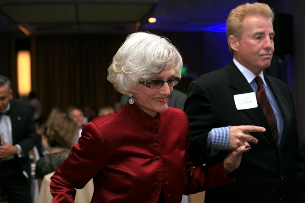 SUN member and event organizer, George Schroeder, helps retired state Senator, Marian Bergeson, up to the stage to receive her SUNshine Award.